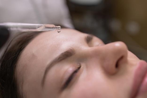 Soins et protection de la peau du visage. une jeune femme au rendez-vous d'une esthéticienne. le spécialiste applique un masque crème sur le visage.