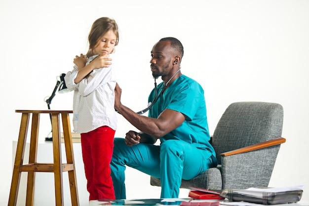 Soins de santé et concept médical - médecin avec stéthoscope à l'écoute de la poitrine de l'enfant à l'hôpital