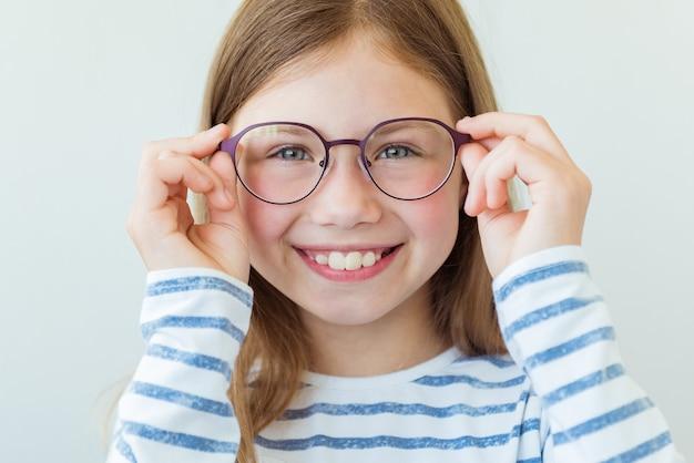 Soins de santé, contrôle du globe oculaire, concept de vision claire. bouchent le portrait d'une charmante écolière à lunettes rouges et violettes
