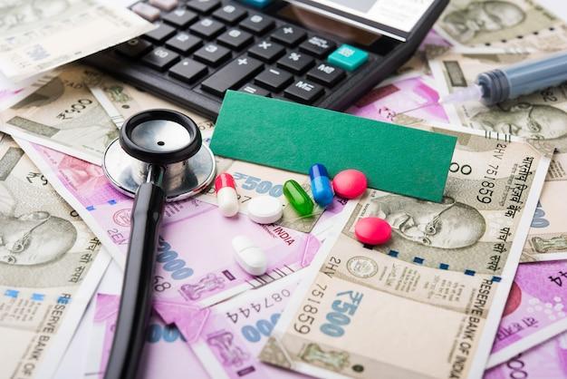 Soins de santé en inde - concept de santé et d'affaires montrant des billets de banque indiens, un stéthoscope, des pilules, une calculatrice, des pommes et un jouet coeur en peluche. mise au point sélective