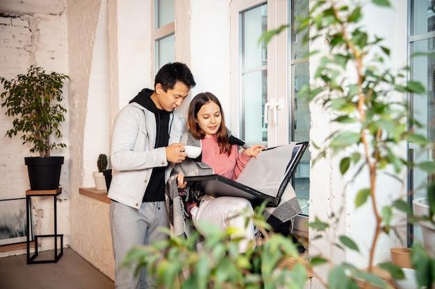 Soir. nouveaux propriétaires, jeune couple emménageant dans une nouvelle maison, un nouvel appartement, l'air heureux. rêve, amour, relation, immobilier et concept d'intérieur. nouvelle vie ensemble. femme caucasienne et homme asiatique.