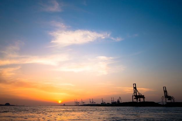 Le soir, la silhouette des grues portuaires