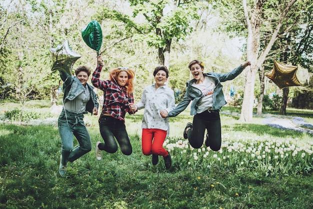 Soirée étudiante en plein air. groupe d'amies gaies souriantes, célébrant une fête avec des ballons dans le parc