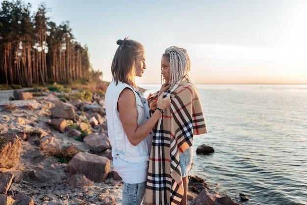 Soirée froide. homme aimant bienveillant donnant son plaid de petite amie sur une froide soirée d'été se reposer près de la rivière