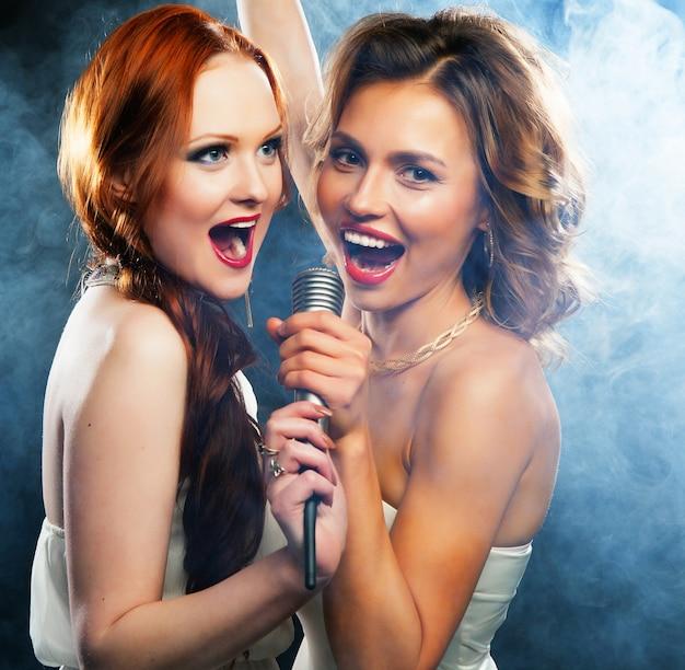 Soirée karaoké. filles de beauté avec un microphone chantant et dansant sur fond sombre.