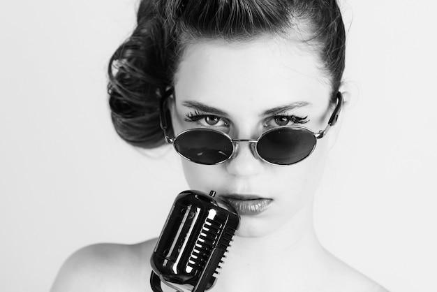 Soirée karaoké. il est temps de chanter. fille chic et bouclée décontractée rétro chantant avec microphone vintage.