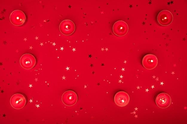 Soirée de noël ou composition de la saint-valentin à base de bougies allumées, paillettes sur une surface rouge. joyeux noël et bonne année, concept happy valentine.