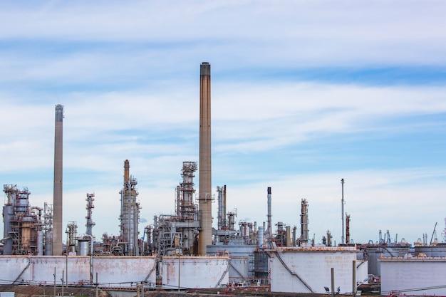 Soirée de scène de la tour de l'usine de raffinerie de pétrole du réservoir et de la colonne d'huile du réservoir de l'industrie pétrochimique ciel bleu et pelouse