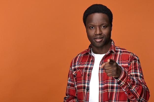 Sois prêt! jeune homme afro-américain attrayant à la mode ayant une expression faciale confiante positive et un index pointé. signes, gestes, symboles et langage corporel