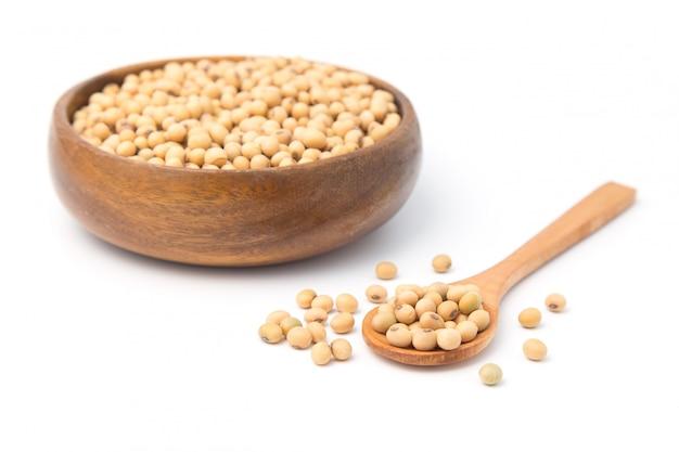 Soja dans un bol en bois et cuillère isolé sur fond blanc.