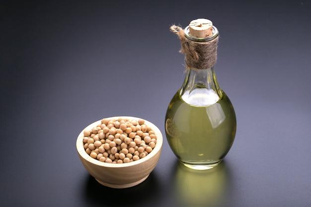 Soja dans un bol en bois et l'huile de soja sur un fond noir