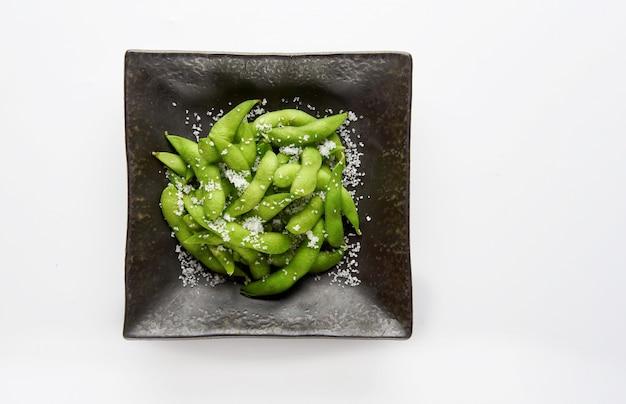 Le soja vert edamame dans le bol, le soja vert frit avec du sel dans un bol noir