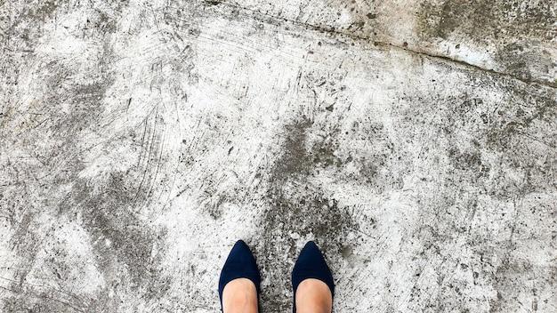 Sol en béton fissuré, texture naturelle. table lumineuse. pieds debout sur le sol.