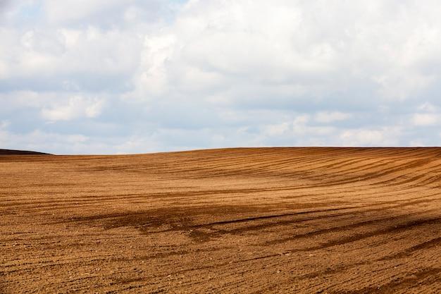Sol brun d'un champ labouré lors de la préparation du sol pour l'ensemencement d'une nouvelle récolte de plantes