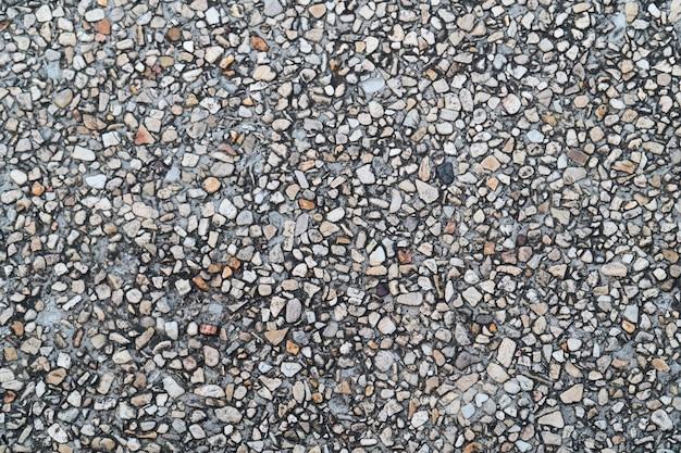 Sol de galets grunge comme fond texturé sans soudure. petits cailloux mélangés avec une texture de sable