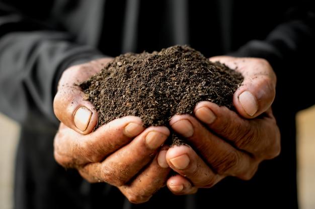 Un sol limoneux riche en mains d'homme.