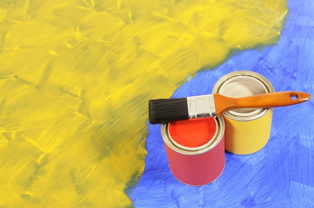 Sol partiellement peint en jaune et bleu avec des pots de peinture