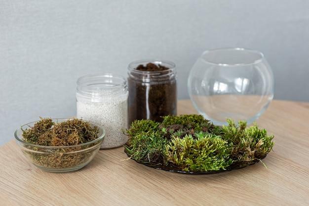 Sol pour transplanter des plantes succulentes à la maison. conteneurs avec de la tourbe, de la perlite et de la mousse sur la table.