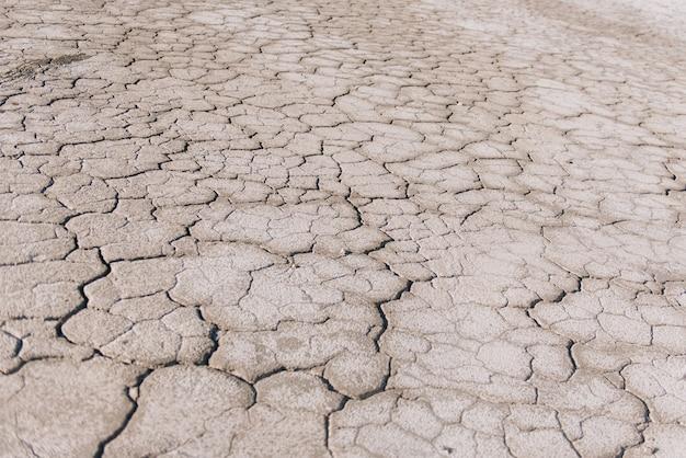 Sol sec brun ou fond de texture de sol fissuré du désert, réchauffement de la terre aride.