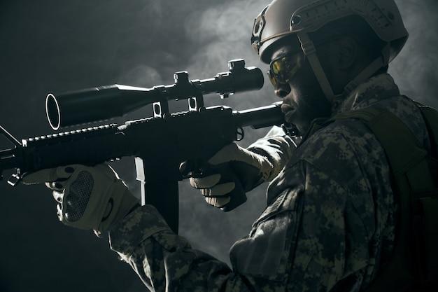 Soldat américain gardant la vue sur une arme à feu moderne.