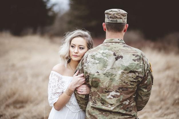 Soldat américain avec sa femme aimante debout dans un champ herbeux sec