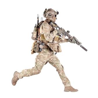 Soldat de l'armée, fantassin équipé, joueur d'airsoft en uniforme de combat de camouflage, casque et casque radio tactique sautant, courant avec un fusil d'assaut à la main en studio isolé sur fond blanc