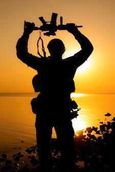 Soldat de l'armée avec fusil au-dessus de sa tête silhouette coucher de soleil. concept de victoire