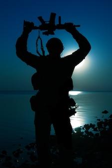 Soldat de l'armée avec fusil au-dessus de sa tête silhouette de lune de nuit. concept de victoire