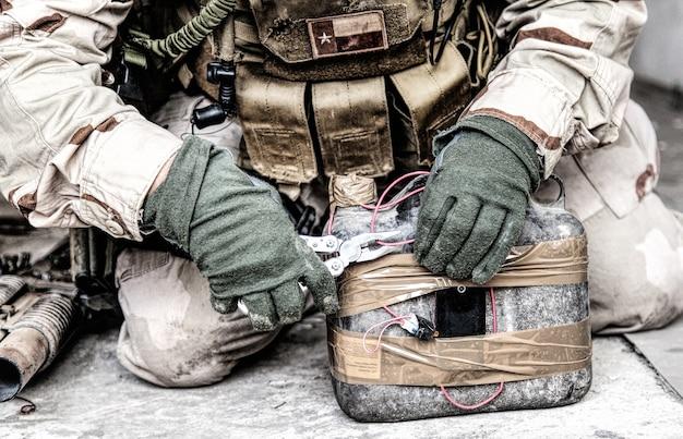 Soldat de l'armée, ingénieur de combat de l'équipe antiterroriste, officier technique en munitions, expert militaire en explosifs utilisant des pinces pour couper le fil sur un engin explosif improvisé, neutralisant une bombe artisanale sur le sol