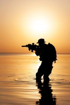 Soldat de l'armée avec silhouette coucher de soleil orange fusil