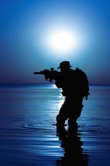 Soldat de l'armée avec silhouette de lune nuit fusil sous le couvert de l'obscurité en action pendant le raid traversant la rivière dans l'eau.