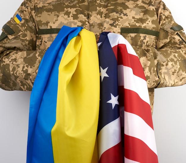 Soldat de l'armée ukrainienne tient les drapeaux de l'ukraine et des états-unis entre ses mains