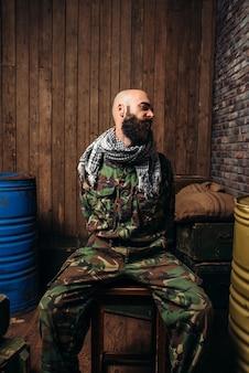 Soldat captif assis attaché à une chaise, horreur de la guerre. terrorisme et terreur, militaire en tenue de camouflage kaki