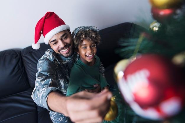 Soldat décorant l'arbre de noël avec sa fille