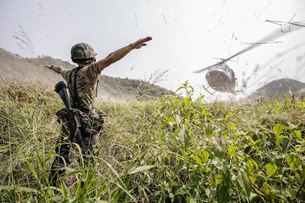 Le soldat donne le signal d'atterrissage pour l'hélicoptère avec le vent dur