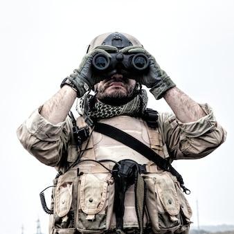 Soldat des forces d'opérations spéciales, éclaireur navy seal en uniforme de combat et casque, regardant à travers des jumelles, observant la zone, cherchant des cibles, surveillant les mouvements ennemis, dirigeant le tir d'artillerie