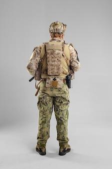 Soldat des forces spéciales avec fusil sur blanc.