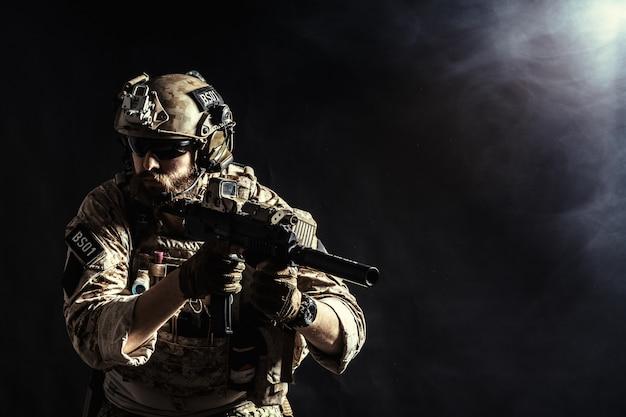 Soldat des forces spéciales avec fusil dans l'obscurité