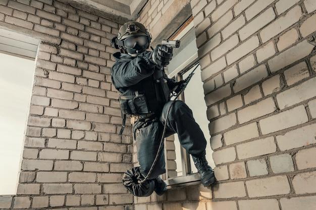 Un soldat des forces spéciales prend d'assaut le bâtiment. écraser