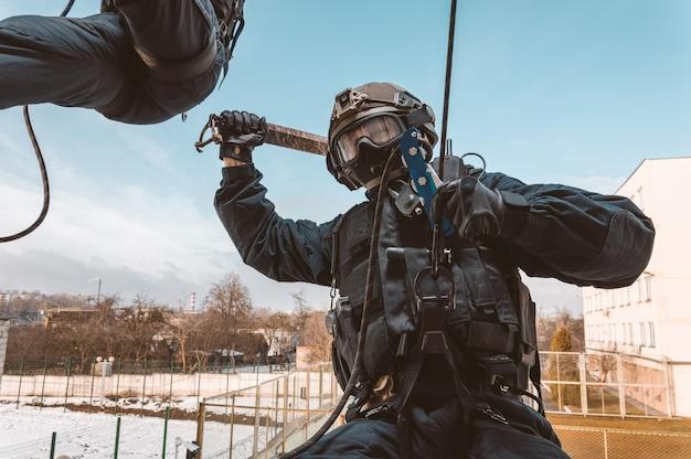 Un soldat des forces spéciales prend d'assaut le bâtiment par la fenêtre. séances de formation de l'équipe swat