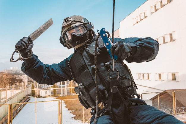 Un soldat des forces spéciales prend d'assaut le bâtiment par la fenêtre