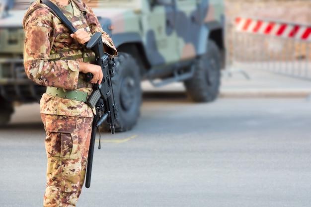 Soldat avec un fusil en uniforme italien près d'une voiture blindée suv militaire.