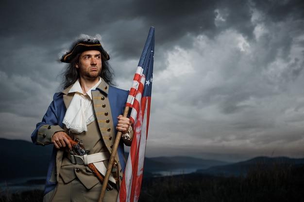 Soldat de guerre de la révolution américaine avec le drapeau des colonies sur un paysage spectaculaire