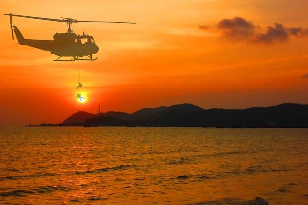 Soldat de largage d'hélicoptère militaire silhouette en service maritime avec fond de nature abstraite ciel coucher de soleil beauté