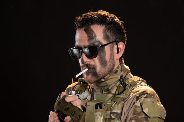 Soldat masculin en camouflage fumant une cigarette sur un mur noir