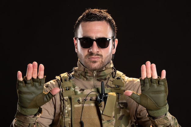 Soldat masculin cool en camouflage se rendant sur un mur noir