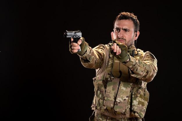 Soldat masculin en tenue de camouflage avec arme à feu sur mur noir