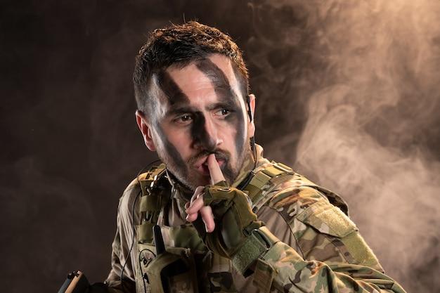 Soldat masculin en tenue de camouflage avec arme à feu sur un mur sombre enfumé