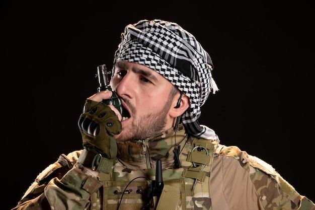 Soldat masculin en tenue de camouflage grenade sur mur noir