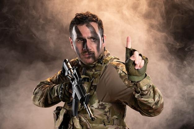 Soldat masculin en tenue de camouflage avec mitrailleuse sur le mur enfumé sombre